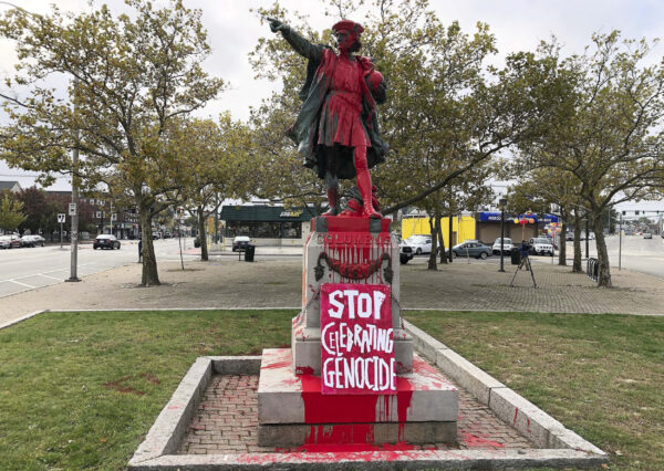 "A sign reading ""stop celebrating genocide"" sits at the base of a statue of Christopher Columbus on Monday, Oct. 14, 2019, in Providence, R.I., after it was vandalized with red paint on the day named to honor him as one of the first Europeans to reach the New World. The statue has been the target of vandals on Columbus Day in the past. (AP Photo/Michelle R. Smith)"