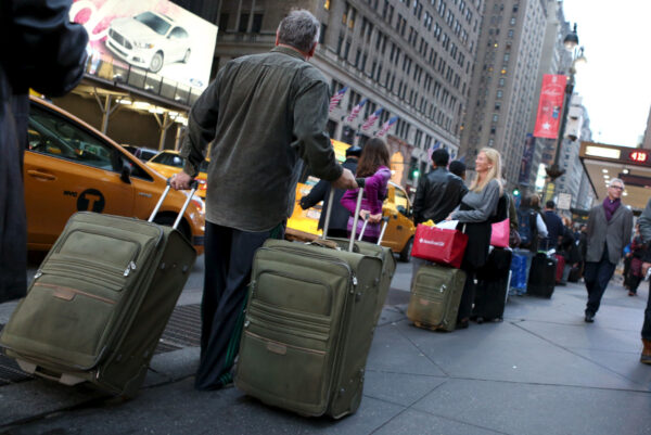 Commuters with suitcases wait at a taxi stand on Seventh Avenue outside of Pennsylvania Station in the Manhattan borough of New York December 27, 2015. REUTERS/Pearl Gabel